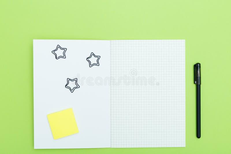 Czarny pióro na rozpieczętowanym pustym copybook i, kłaść na zielonym tle z kopii przestrzenią, minimalny styl Mieszkanie nieatut obrazy stock