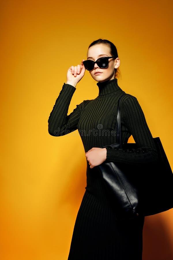 Czarny Piątek sprzedaży pojęcie Zakupy kobieta trzyma czarną rzemienną torbę odizolowywająca na żółtym tle fotografia royalty free