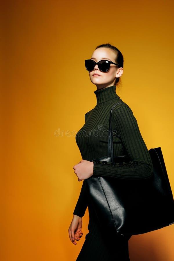 Czarny Piątek sprzedaży pojęcie Zakupy kobieta trzyma czarną rzemienną torbę odizolowywająca na żółtym tle fotografia stock