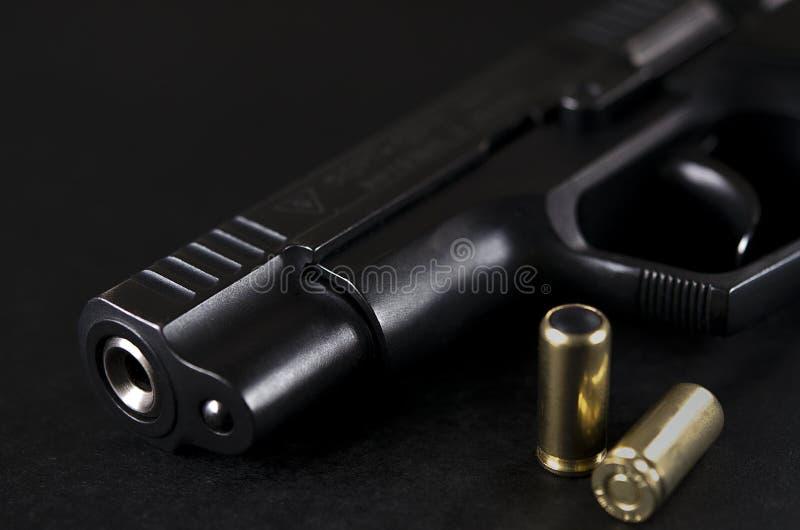 Czarny pistolet kłama na czarnym tle obok pocisków zdjęcia royalty free