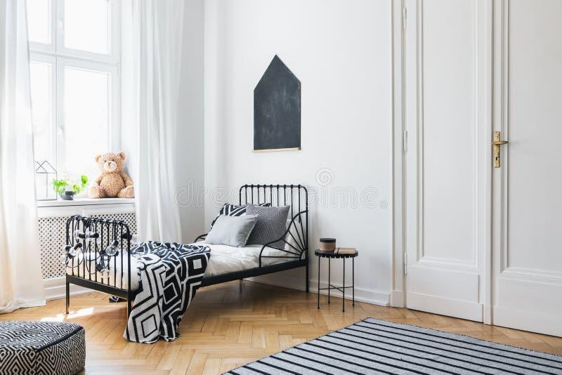 Czarny plakat nad łóżko z wzorzystymi prześcieradłami obrazy stock