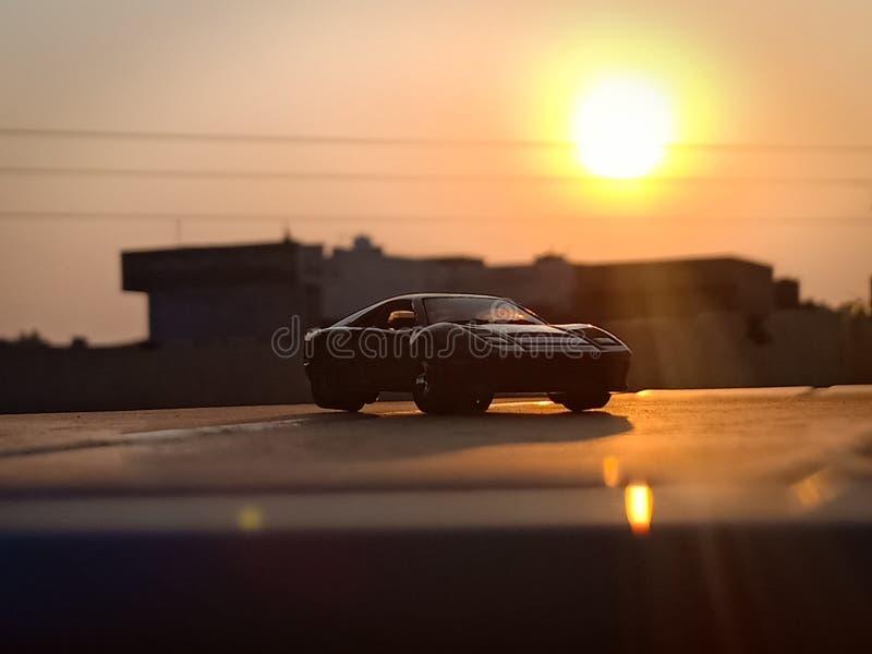 Czarny położenia słońce i samochód fotografia stock