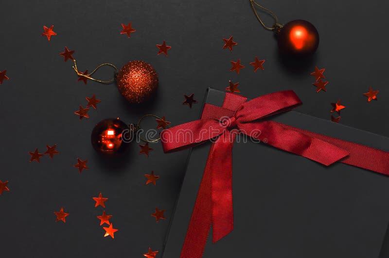Czarny prezenta pudełko z czerwonym faborkiem, Bożenarodzeniowe piłki, czerwoni holograficzni błyskotliwość confetti na ciemnym t zdjęcie stock