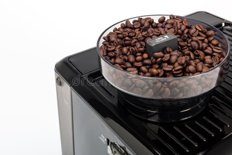 Czarny ręczny kawowy producent na białym tle, ostrzarz z świeżymi kawowymi fasolami wyszczególnia odgórnego widok obrazy stock