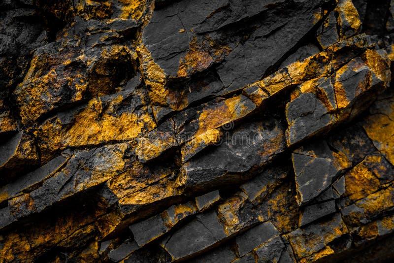 Czarny rockowy tło z złotem, kolorem żółtym barwiącymi/kołysa fotografia stock