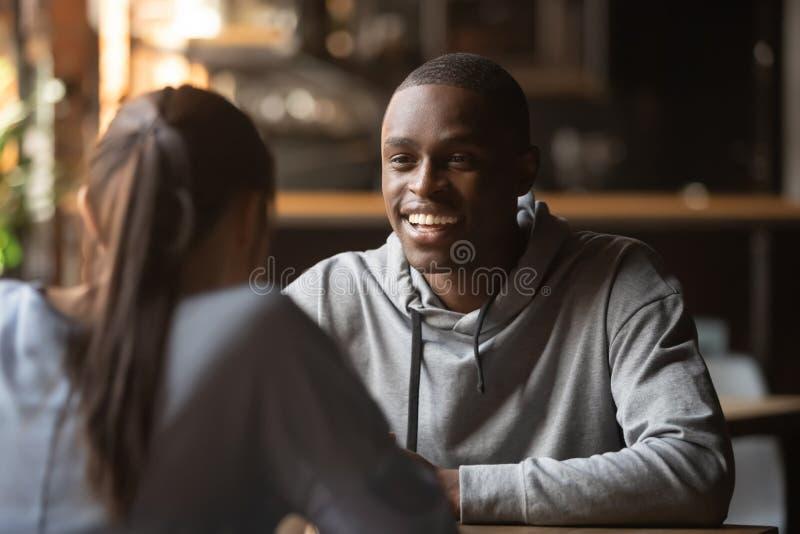 Czarny rozochocony faceta gawędzenie z dziewczyną podczas prędkości datowanie fotografia stock