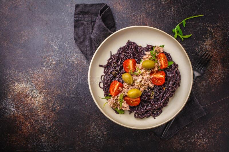 Czarny ryżowy makaron z tuńczykiem, pomidorami i oliwkami w białym talerzu, odgórny widok obraz royalty free