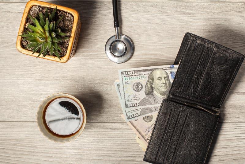 Czarny rzemienny portfel z dolarowymi rachunkami, filiżanka kawy, phonendos zdjęcie stock