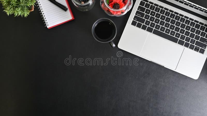 Czarny, skórzany stół biurowy z komputerem przenośnym, filiżanką kawy i materiałów biurowych obraz royalty free