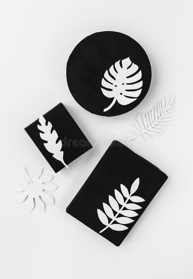Czarny skandynawa stylu prezent ustawiający z białym tropikalnym papierem opuszcza fotografia royalty free
