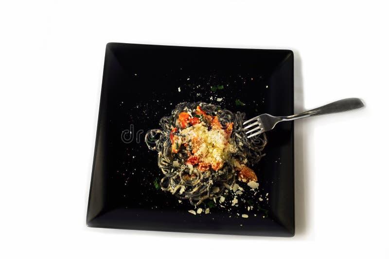 Czarny spaghetti z czosnkiem, pomidorem, ricotta, grulą i parmesan, obraz royalty free