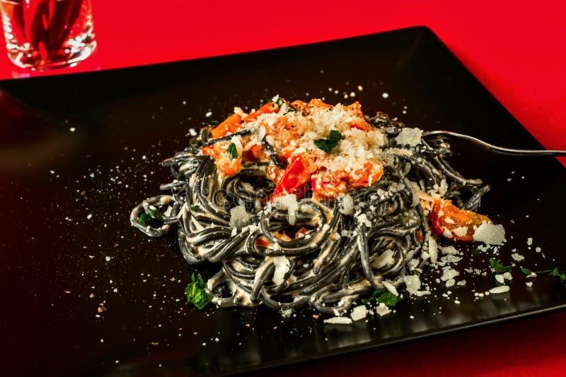 Czarny spaghetti z piec pomidorem, chili pieprzem, ricotta i parmasan serem, fotografia royalty free