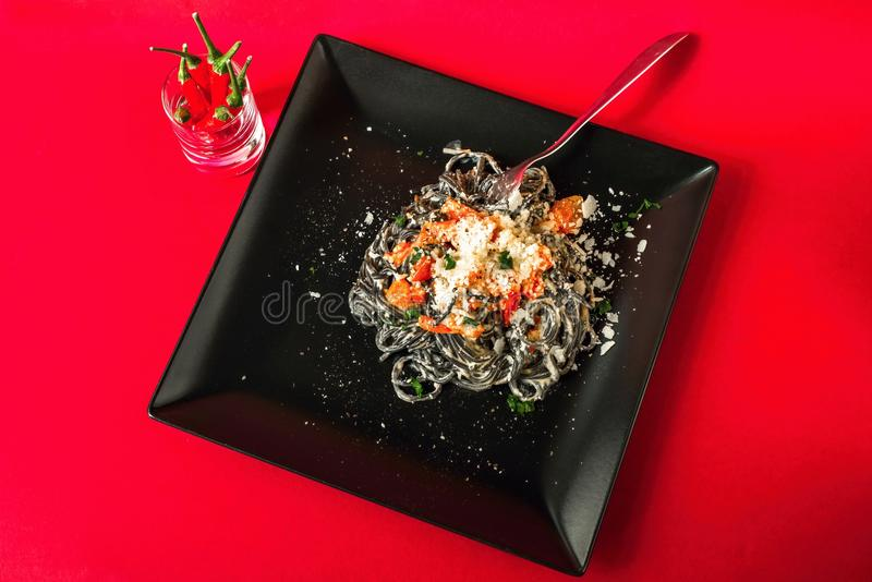 Czarny spaghetti z pomidorem, ricotta i parmasan serem na czarnym talerzu na czerwonym tle, obrazy royalty free