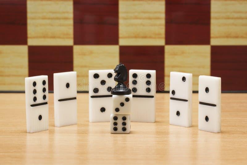 Czarny szachowy koń na kostka do gry i dominach zdjęcia stock