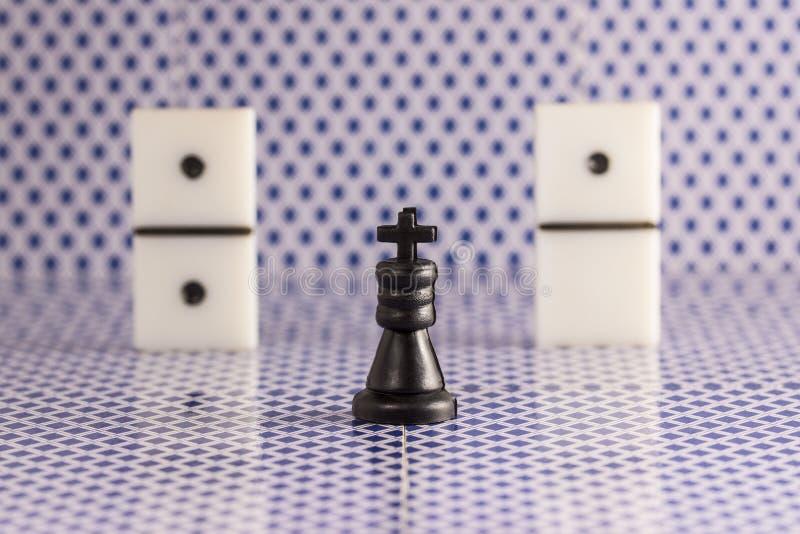 Czarny szachowy królewiątko i kostka do gry dla domin na zamazanym tle tylna strona karta do gry obrazy stock