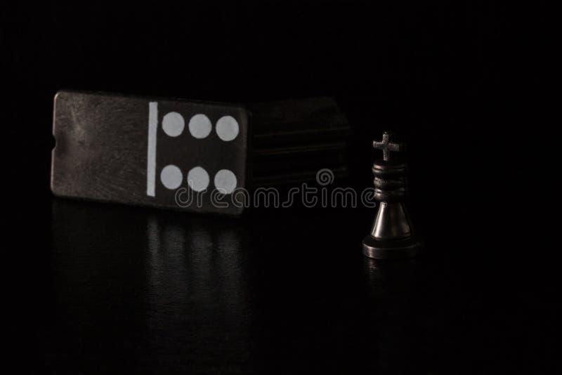 Czarny szachowy królewiątko i kostka do gry dla domina na ciemnym tle obraz royalty free