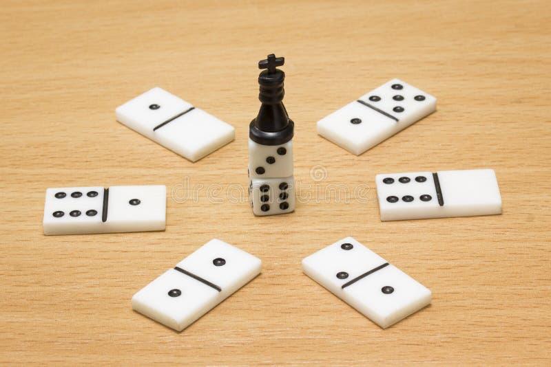 Czarny szachowy królewiątko na wierzchołku kostka do gry wokoło kłamstw domin zdjęcia royalty free