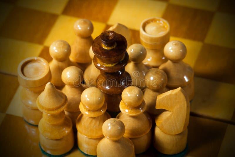 Czarny szachowy królewiątko otaczający białymi kawałkami zdjęcia stock
