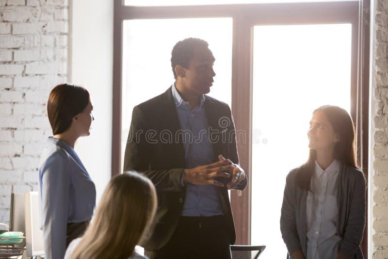 Czarny szef daje instrukcjom pracownicy podczas odprawy przy biurem zdjęcia stock