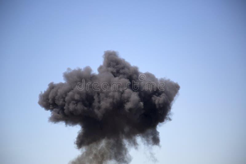 Czarny sztuczny dym w niebieskim niebie zdjęcie royalty free