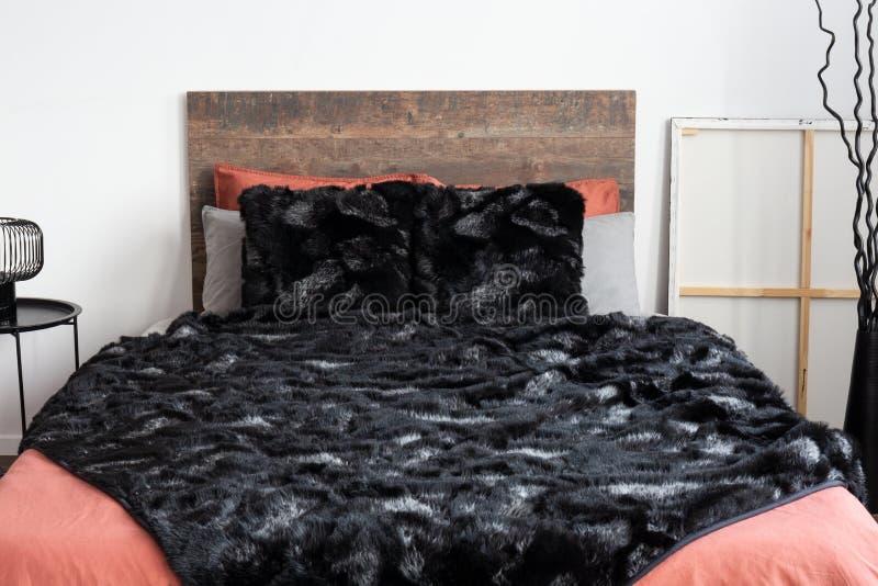 Czarny sztuczny futerko kłaść na koralowej pościeli w białej sypialni obraz royalty free
