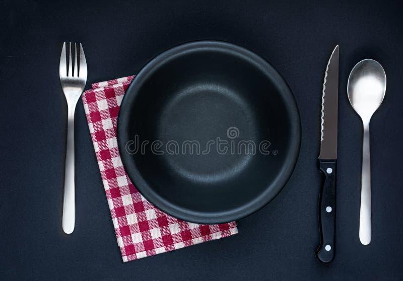 Czarny talerz, cutlery i czerwona w kratkę pielucha na czarnym stołowym odgórnym widoku, Zg?asza po?o?enie Mieszkanie nieatutowy obrazy stock