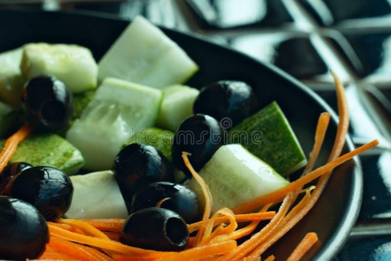 Czarny talerz z kolorowymi jaskrawymi warzywami na czarnym stole zdjęcie royalty free