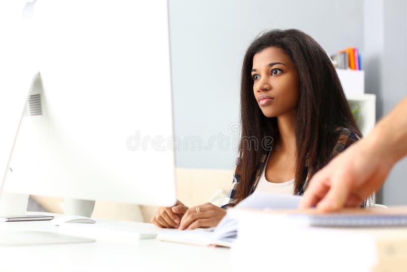 Czarny uśmiechnięty kobiety obsiadanie przy miejsce pracy pracuje z komputerem stacjonarnym zdjęcie royalty free
