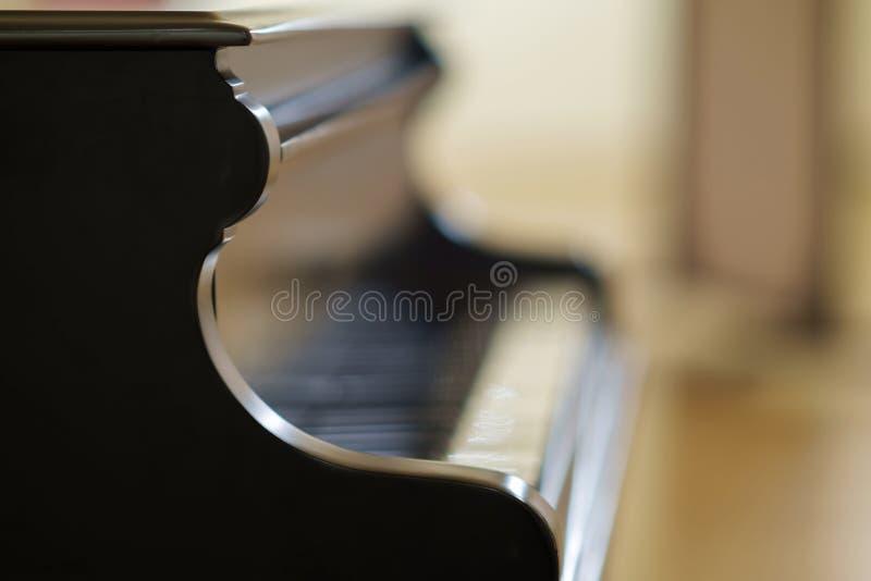 Czarny uroczysty pianino z rozmytym tłem obraz stock