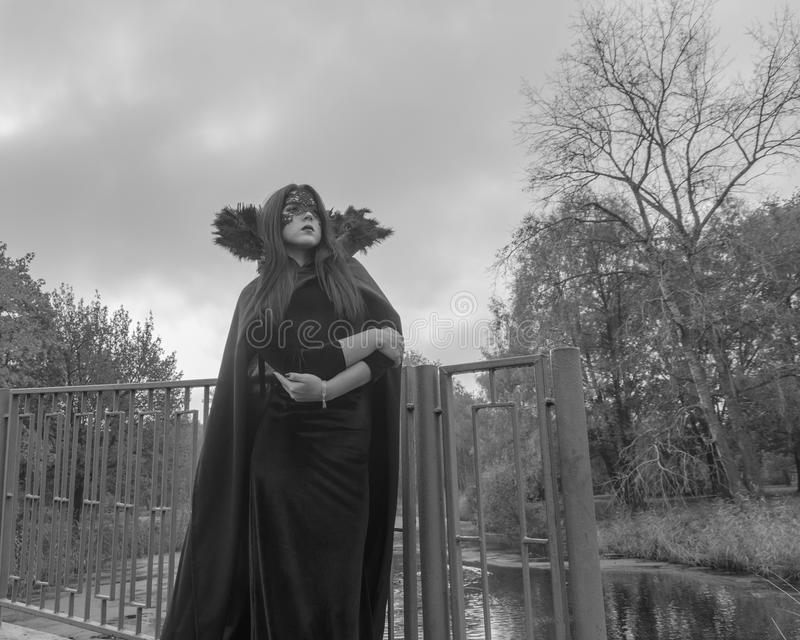czarny white Dziewczyna w masce i kontusze na ciemnym tle niebo wizerunek Halloween fotografia royalty free