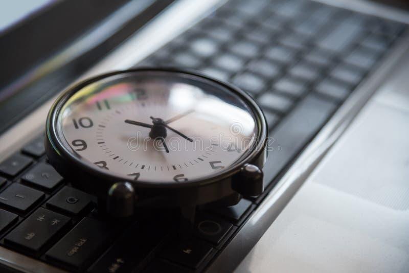 Czarny zegar kłaść na klawiaturowym czas metafory pojęciu w ciemnej depresji ke zdjęcia stock