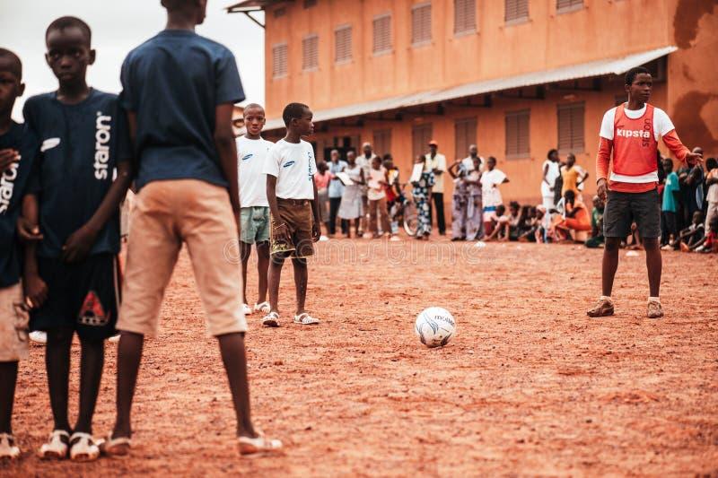 Czarnych Afrykanów dzieci, chłopiec i dorosli bawić się piłkę nożną, obrazy stock