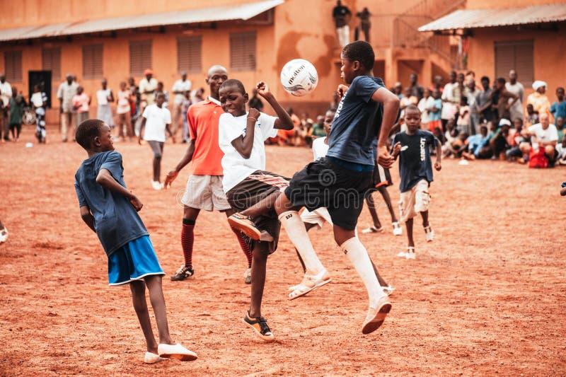 Czarnych Afrykanów dzieci, chłopiec i dorosli bawić się piłkę nożną, zdjęcie stock