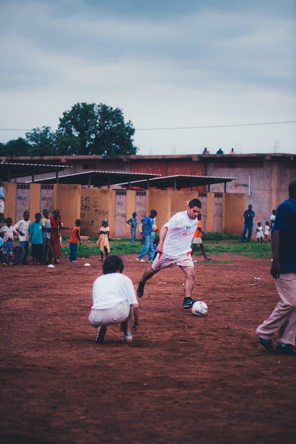 Czarnych Afrykanów dzieci, chłopiec i dorosli bawić się piłkę nożną z caucasian wolontariuszami, obrazy stock