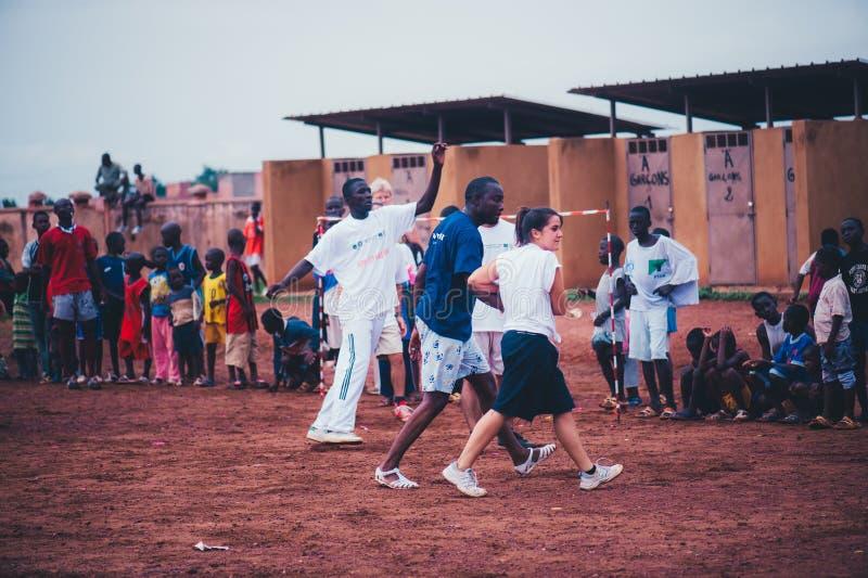 Czarnych Afrykanów dzieci, chłopiec i dorosli bawić się piłkę nożną z caucasian wolontariuszami, zdjęcia stock