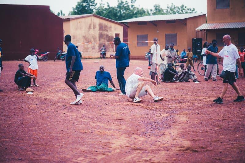 Czarnych Afrykanów dzieci, chłopiec i dorosli bawić się piłkę nożną z caucasian wolontariuszami, obraz stock