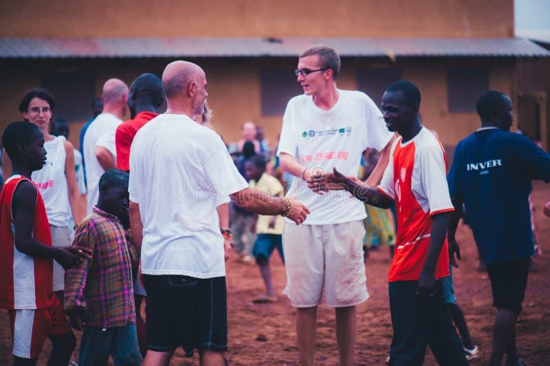 Czarnych Afrykanów dzieci, chłopiec i dorosli bawić się piłkę nożną z caucasian wolontariuszami, fotografia stock