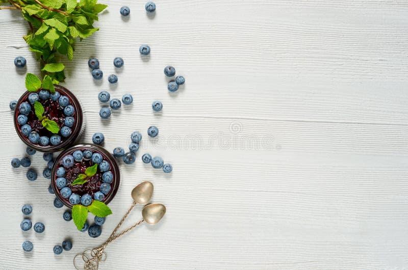 Czarnych jagod smoothies z świeżymi nowymi liśćmi na szarym tle Lata detox superfoods śniadanie lub zdrowy deser obraz stock