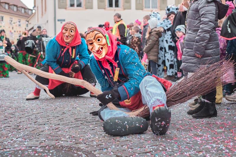 Czarodziejska czarownica w czerwonym błękitnym kostiumu z siedzi w ulicie Uliczny karnawał w południowym Niemcy - Czarny las fotografia stock