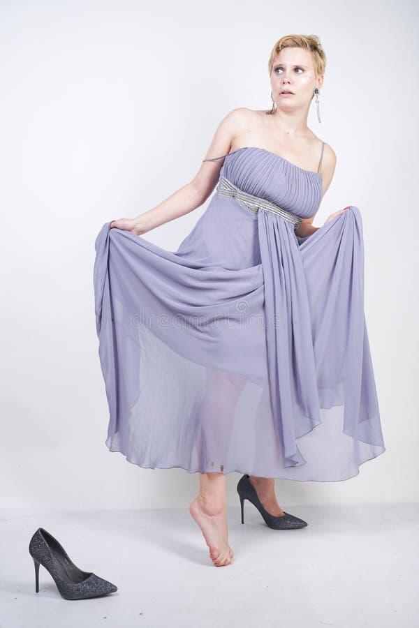 Czarować plus wielkościowa młoda kobieta w popielatej togi sukni gubił kapeć na białym tle w studiu piękna pyzata krótkiego włosy obraz stock