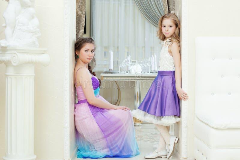 Czarowni potomstwo modele pozuje w eleganckich sukniach fotografia stock