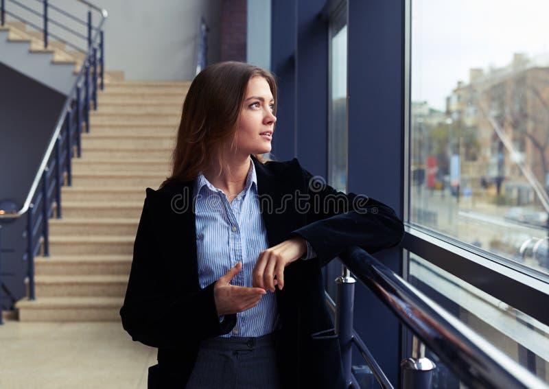 Czarująca kobieta patrzeje przez okno zdjęcie stock