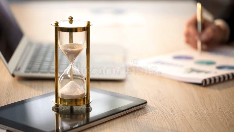 Czas biega w hourglass, żeński kierownik sprawdza wykresy przy biurowym biurkiem obrazy royalty free