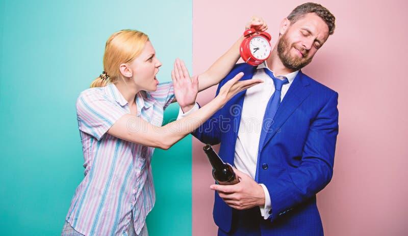czas co M??czyzna cierpienie od alkoholizmu Biznesmen z alkohol kobiet? z budzikiem i butelk? Gniewna ?ona zdjęcie royalty free