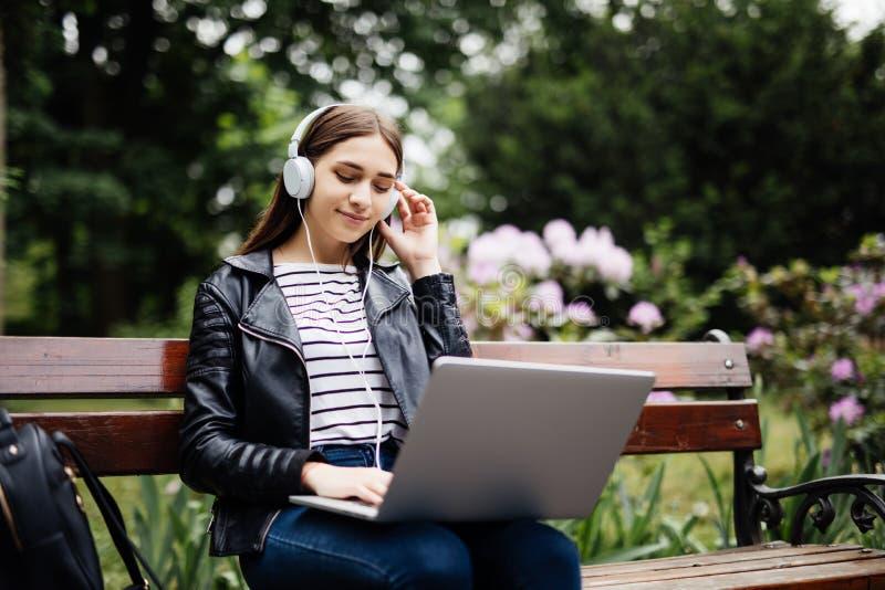 Czas dla małego spoczynkowego Studenckiego obsiadania na ławce słucha muzyka, używa laptop i jest ubranym hełmofony w kampus norm zdjęcia royalty free