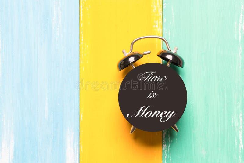 Czas jest pieniądze czarny budzik na kolorowych tło z sformułowanie czasem jest pieniądze obraz royalty free