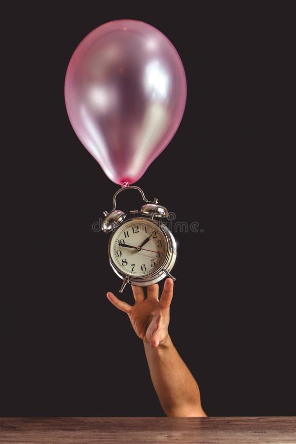 Czas lata pojęcie - obrazek someone ` s ręka próbuje dosięgać starego metalu zegar który dołącza różowy balon obrazy royalty free