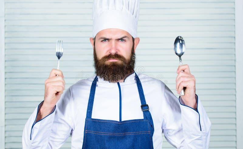 Czas próbować smak Szef kuchni twarzy chwyta poważna łyżka i rozwidlenie Mężczyzna przystojny z brodą trzyma kitchenware na biały zdjęcia royalty free