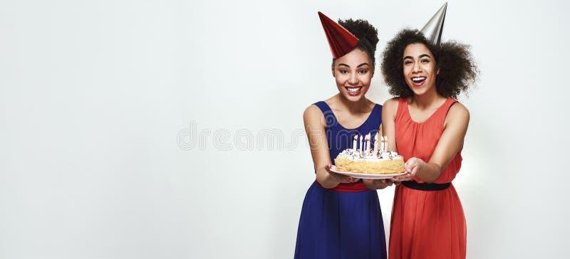 Czas robić życzeniu! Szeroka fotografia szczęśliwe młode afro amerykańskie kobiety trzyma tort z świeczkami w partyjnych kapelusz zdjęcie royalty free