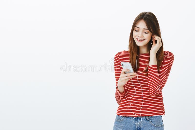 Czas rozweselać up z muzyką w ucho Portret stawia na słuchawkach i podnosi piosenkę śliczna czuła europejska dziewczyna, zdjęcie royalty free
